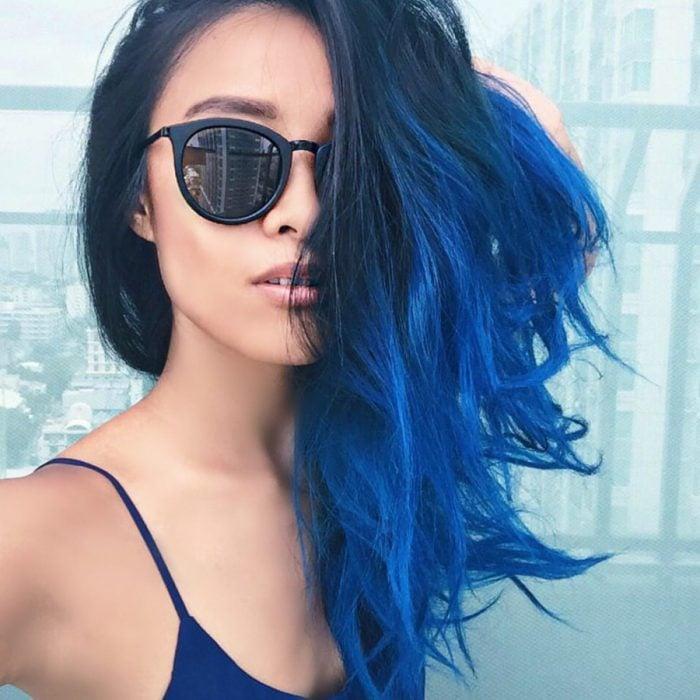 mujer morena lentes oscuros cabello azul