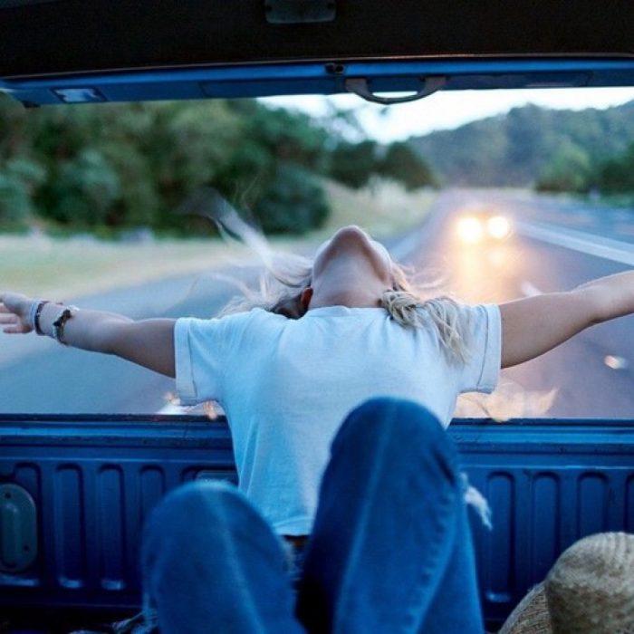 mujer en camioneta hace sus brazos para atrás