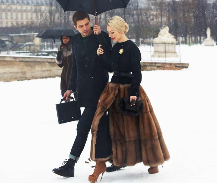 homre le da sombrilla a mujer rubia caminando en la nieve