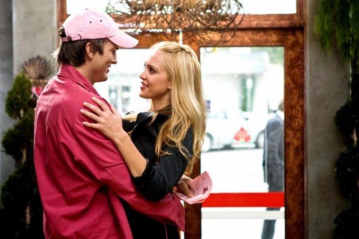 hombre con gorra rosa y mujer rubia abrazados