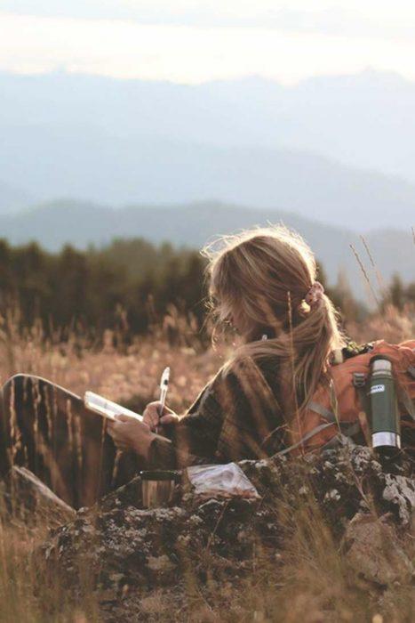 chica en la montaña escribiendo