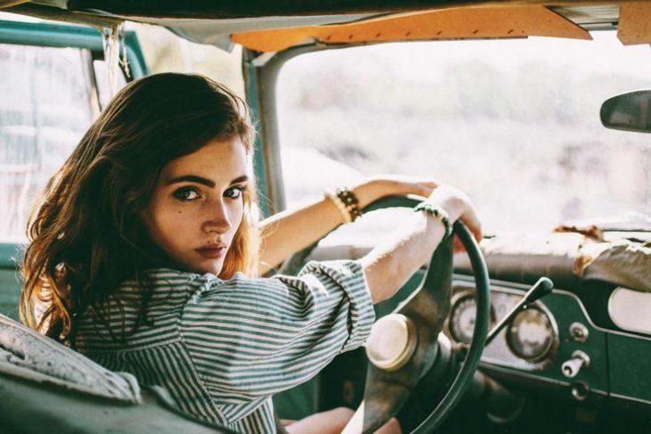 chica al volante de coche antiguo