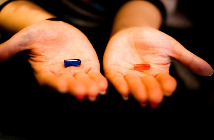 manos con píldora azul y roja