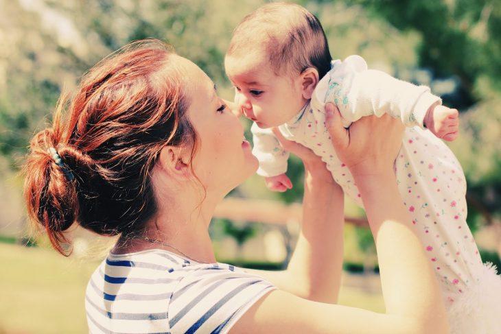 mujer cargando bebé en brazos