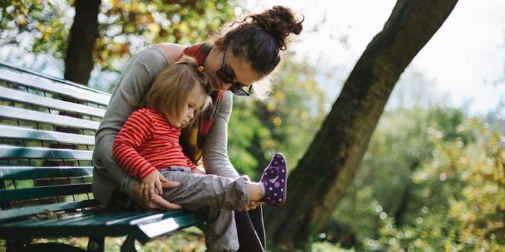 mujer con niña en banca del parque