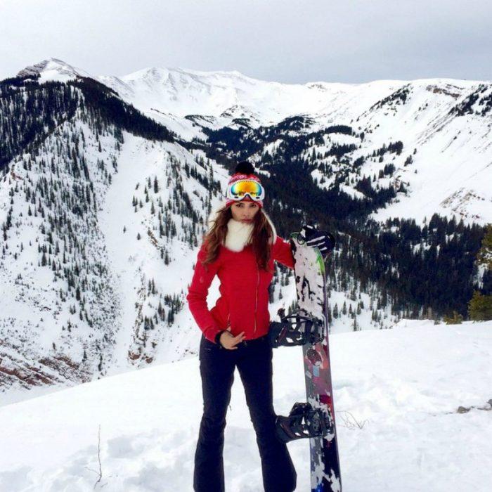 mujer en las montañas nevadas con patineta snowboard