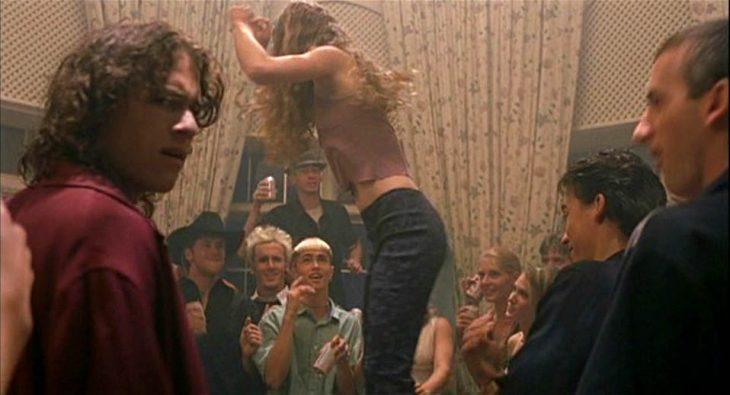 mujer rubia arribe de una mesa bailando