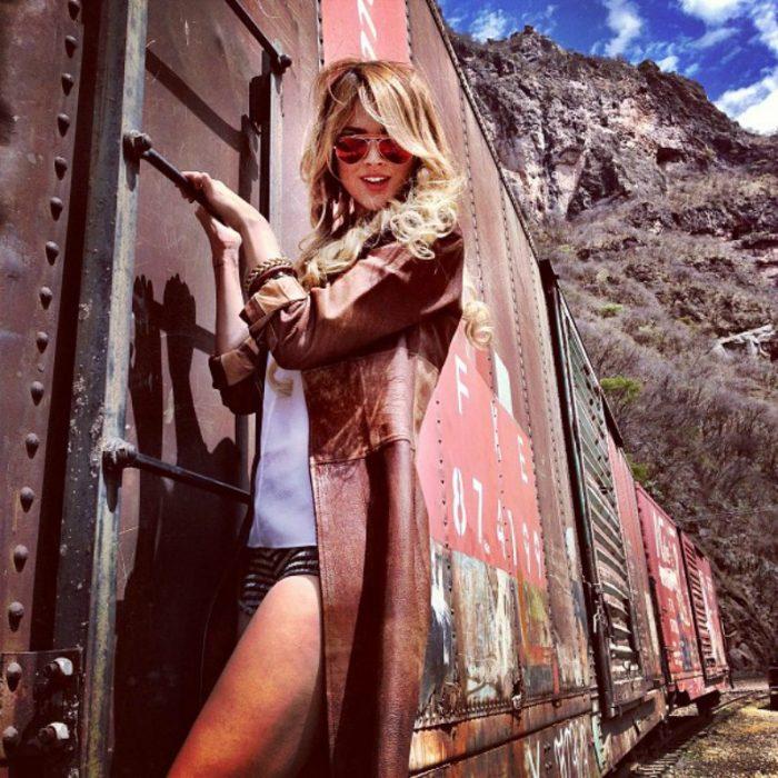 mujer rubia colgada de un tren
