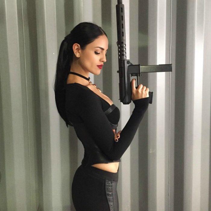 mujer de cabello negro con metralleta