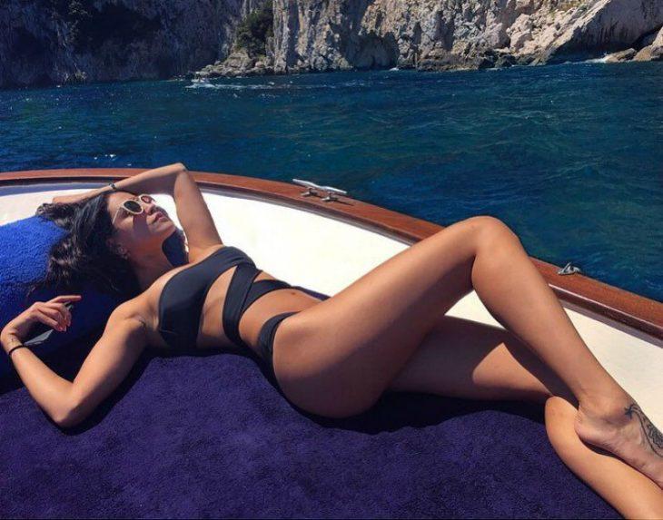 mujer en traje de baño en yate tomando el sol