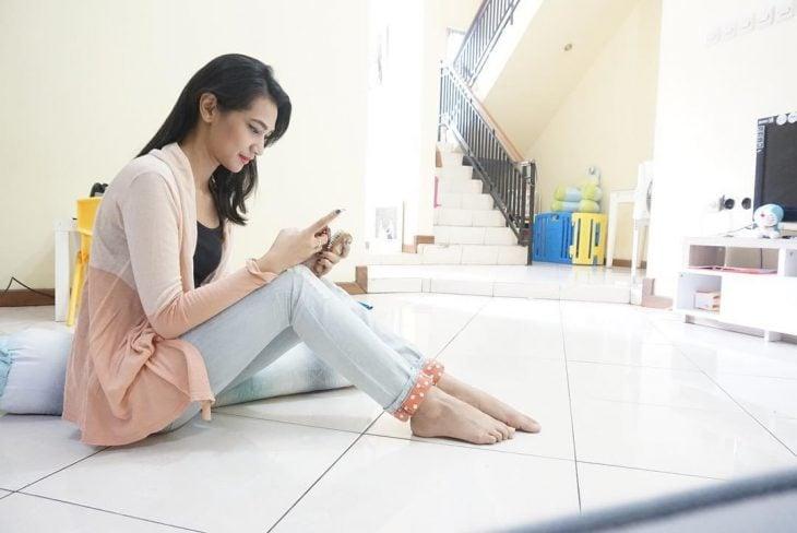mujer morena sin zapatos sentada en el suelo