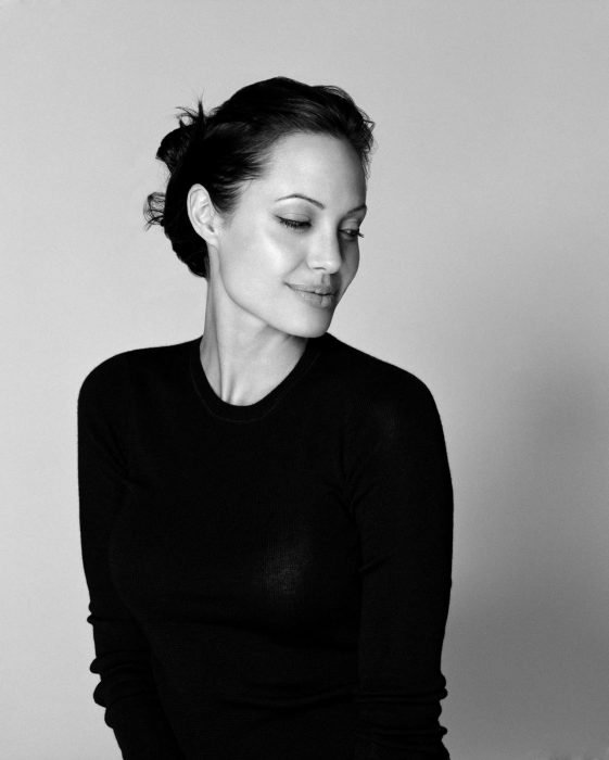 mujer de camisa negra y pelo negro sonríe y mira hacia abajo
