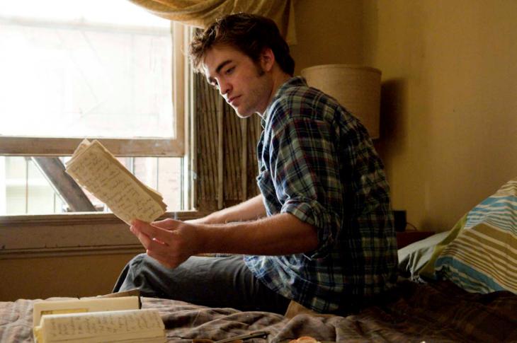 Robert Pattinson leyendo unas hojas que están sobre una cama en la película remember me