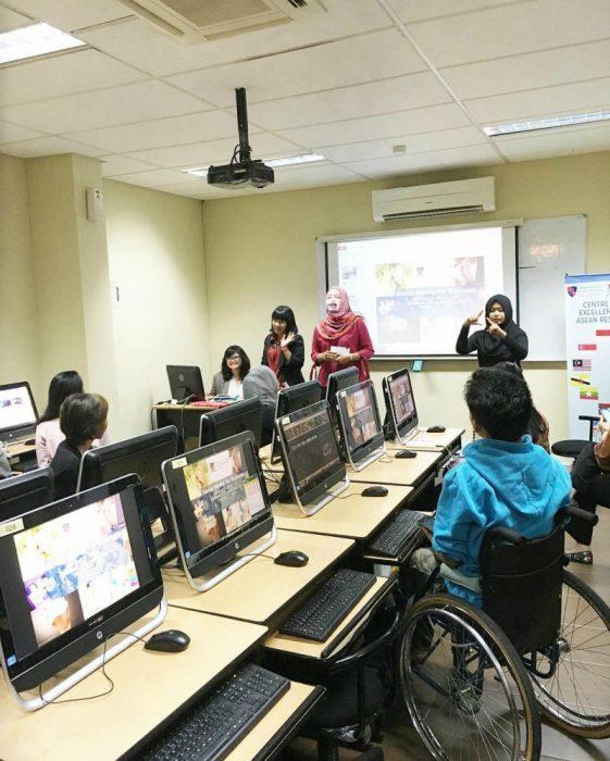 sala de juntas con computadoras y hombre en silla de ruedas