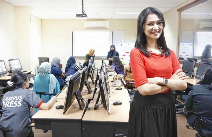 sala de juntas con computadoras y mujer sonriendo blusa roja