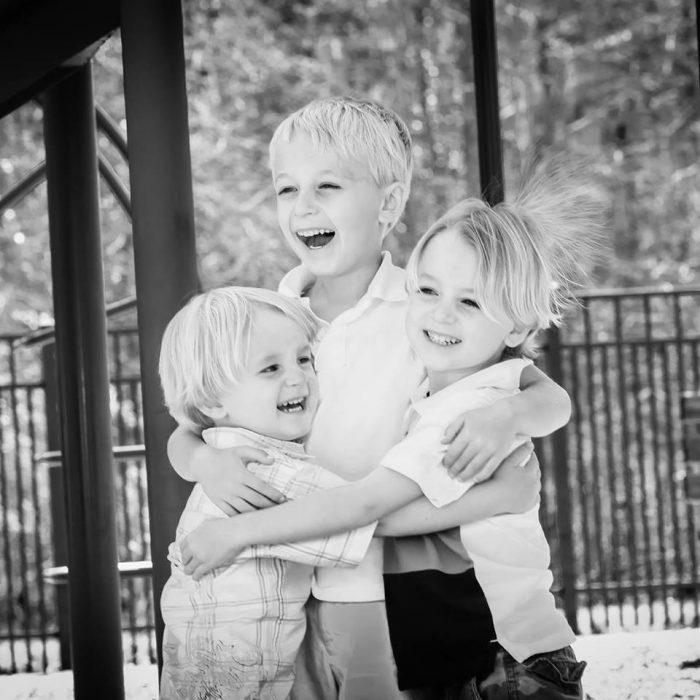tres niños abrazados sonriendo