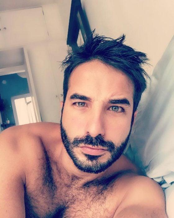 hombre sin playera acostado en la cama ojos azules