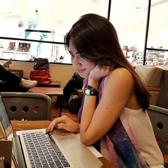 mujer morena seria trabajando en computadora