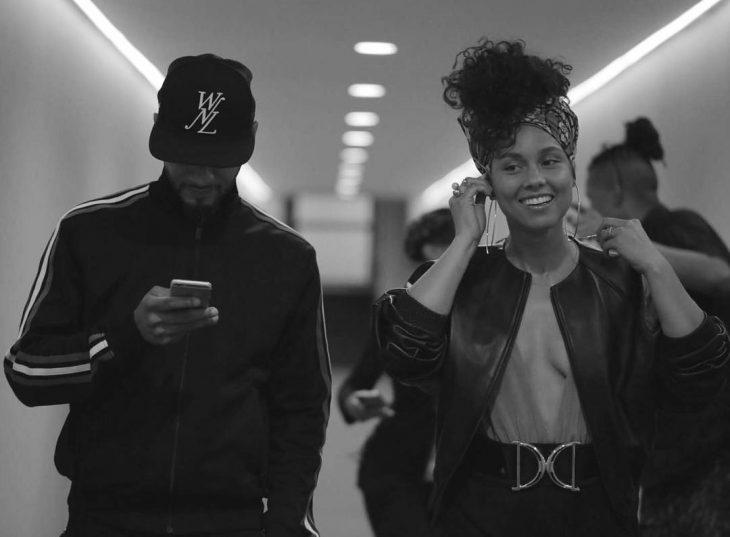 hombre con gorra mirando celular y mujer con aretes y chaqueta