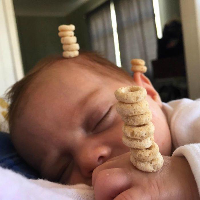 pequeño bebé en brazos dormido con pila de cereal en su frente