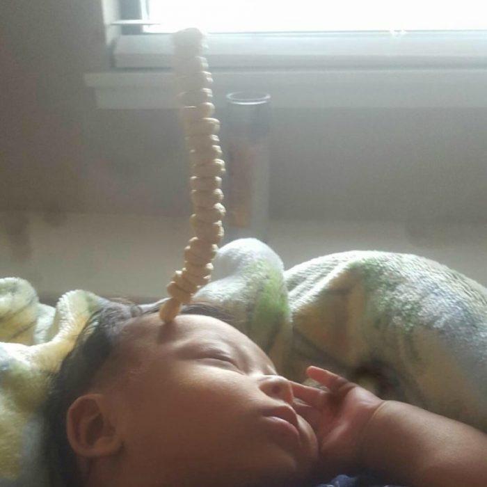pequeño bebé dormido con pila de cereal en su frente