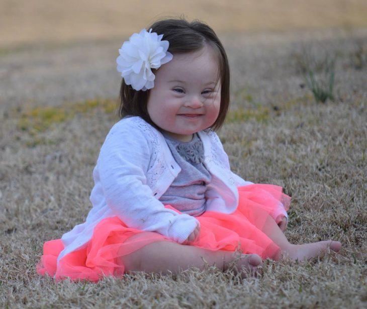 niña con vestido rosa y flor en la cabeza