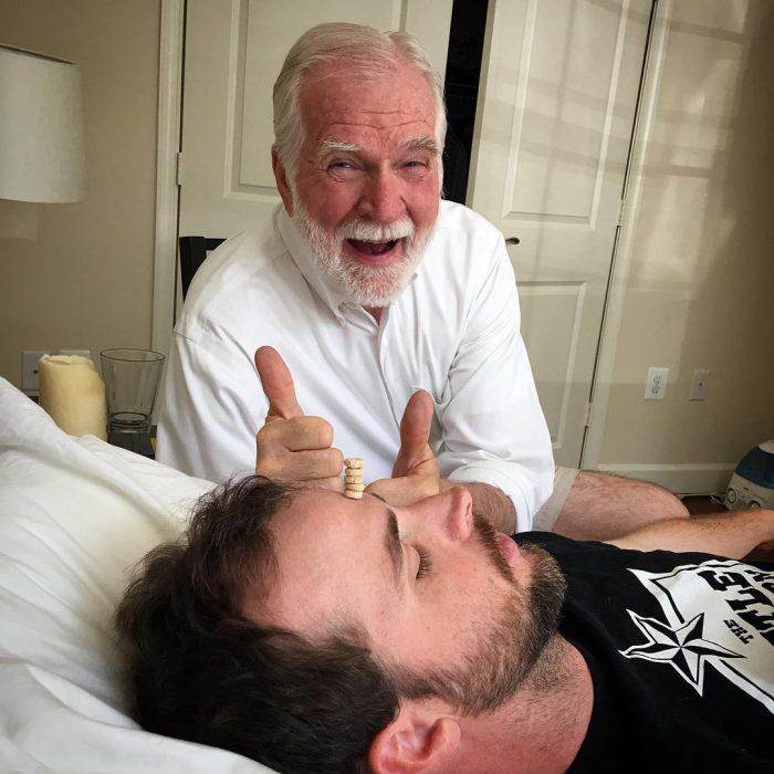 señor con canas poniendo pila de cherios en la cara de su hijo dormido