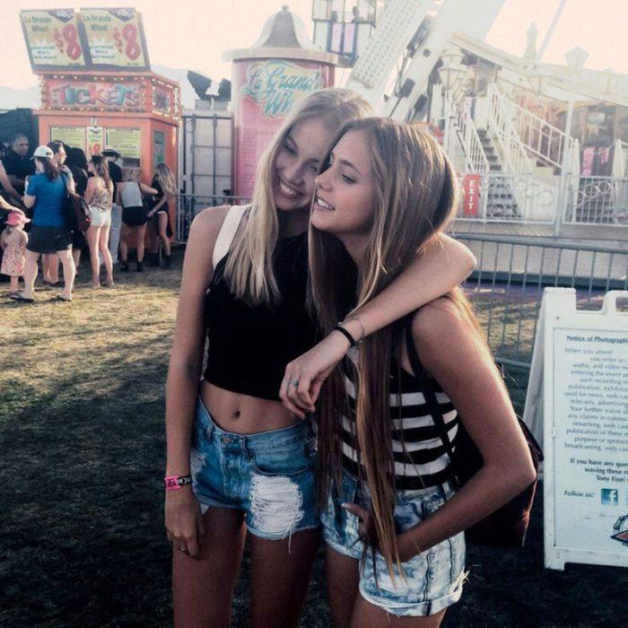 par de amigas rubias se abrazan sonriendo en parque de diversiones