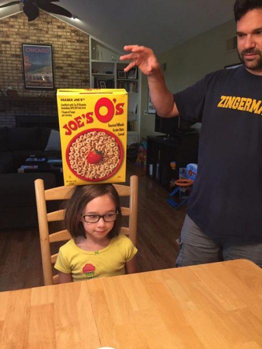 niña con caja de cereal en la cabeza