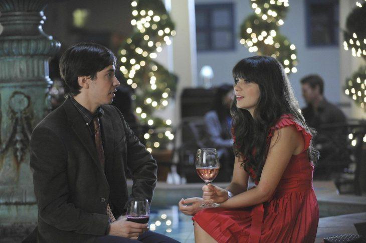 Escena de la serie new girl. Chica conversando con un chico mientras toman vino