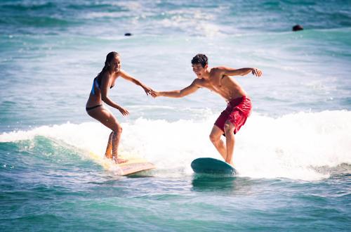 Pareja de amigos practicando surf en el mar mientras se toman de las manos
