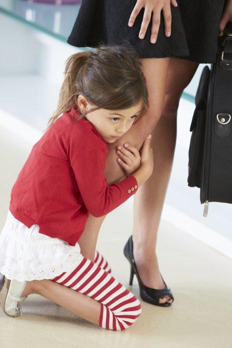 niña abrazada de la pierna de mujer