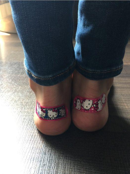 chica con curitas de kitty en los tobillos