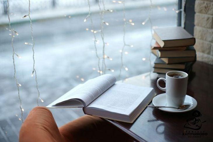 libro y café sobre mesa frente a ventana