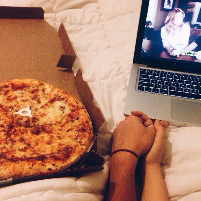 pareja tomados de la mano con pizza y computadora en cama