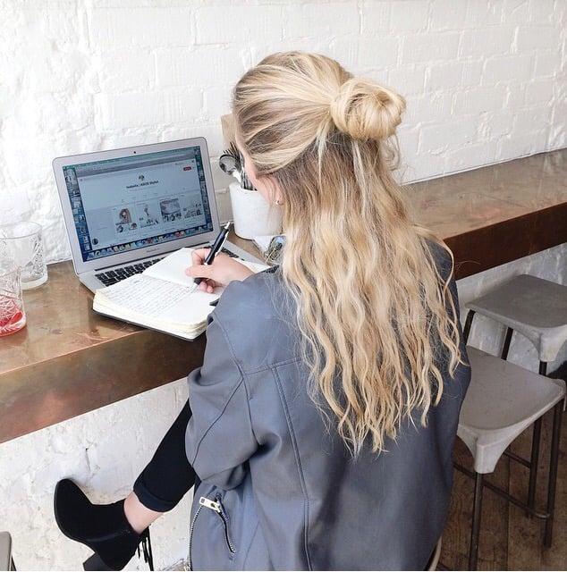 Chica sentada frente a un escritorio escribiendo en una libreta