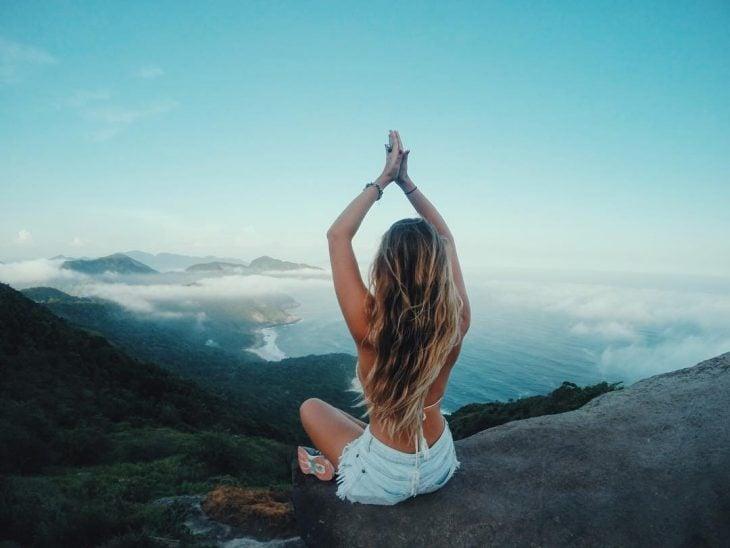 Chica sentada en el filo de una montaña haciendo posiciones de yoga
