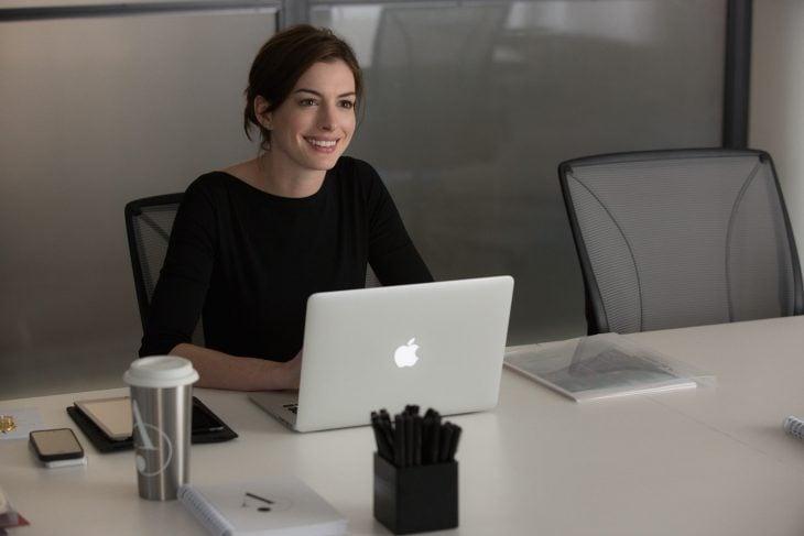 Escena de la película pasante de moda. Anne Hathaway revisando su computadora