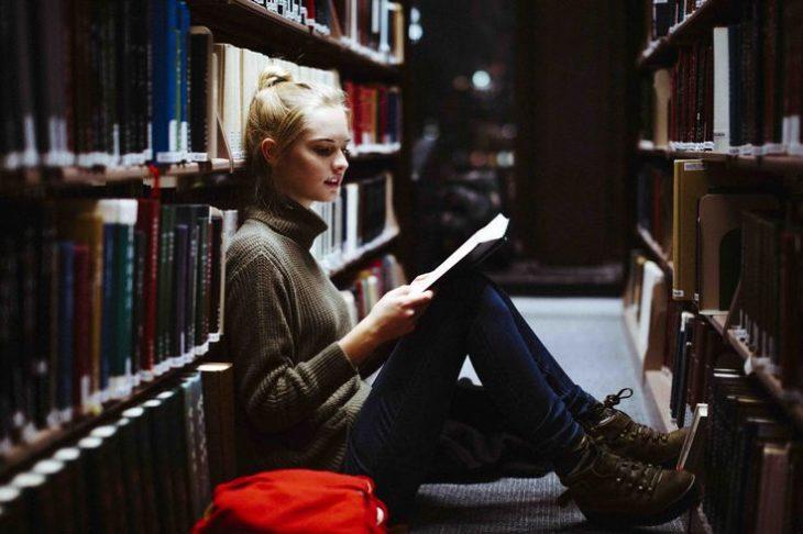 Chica sentada sobre una estantería de libros en la biblioteca
