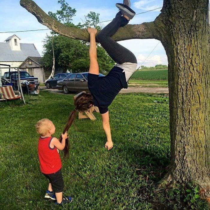 niño jalando el cabello de chica colgando de un árbol