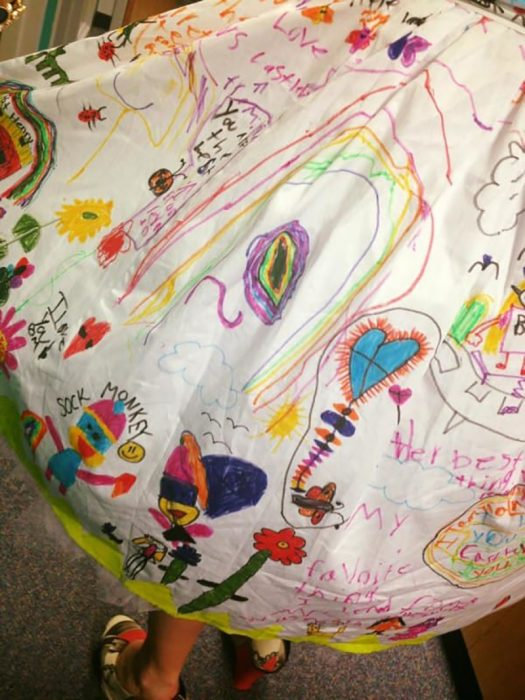 tela de color blanco con dibujos y firmas de niños