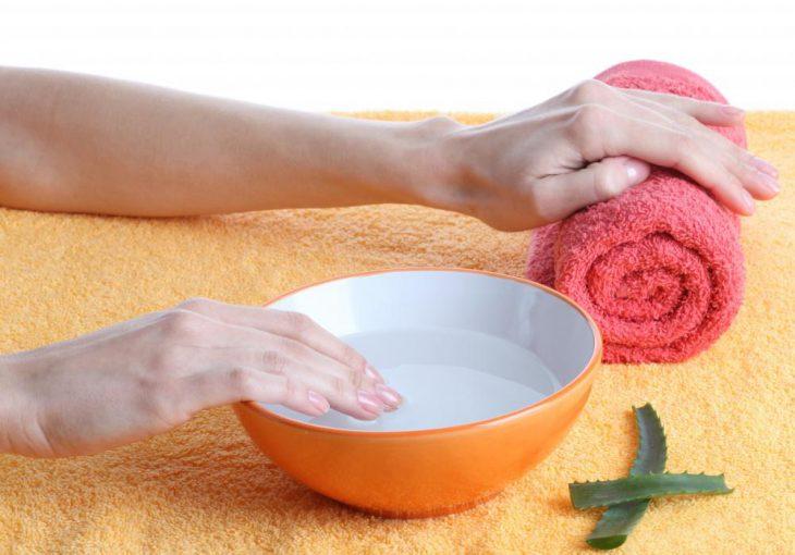 Chica sumergiendo sus uñas en agua caliente para iniciar con una manicura