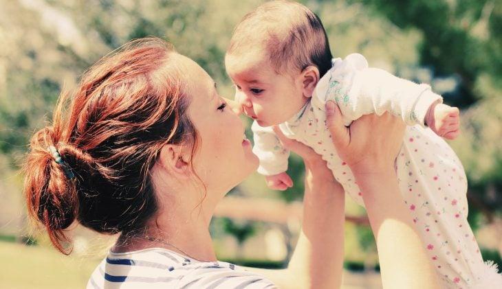 mujer con bebé sonriendo y levantandolo en brazos