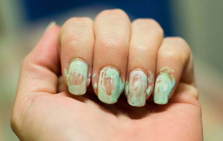 Uñas de una chica arruinadas con el esmalte