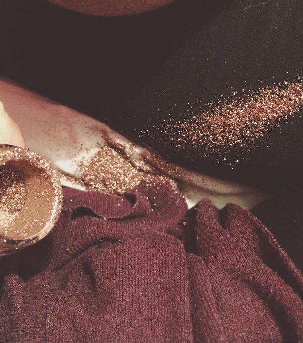 Polvo de maquillaje derramado sobre la ropa de una chica