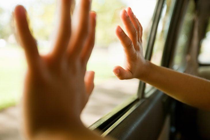 manos recargadas en vidrio de coche