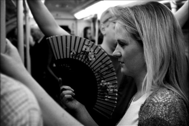 chica en metro con abanico