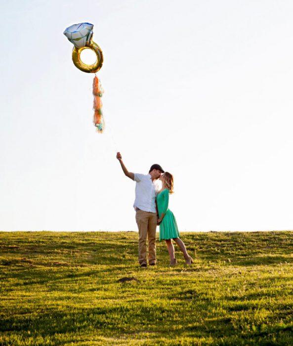 Pareja anunciando su compromiso con un globo de helio