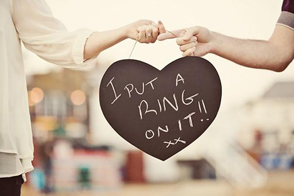 Pareja de novios anunciando su compromiso con un corazón enorme