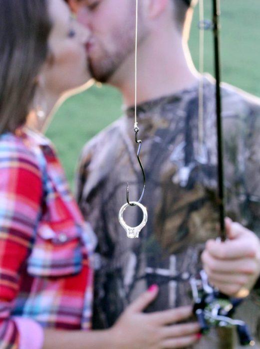 Pareja de novios anunciando su compromiso mientras el sostiene un anillo con una red de pesca